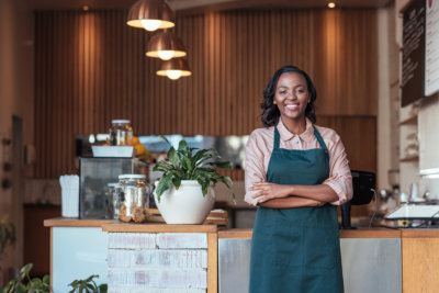young African female entrepreneur smiling and standing welcomingly in her trendy cafe